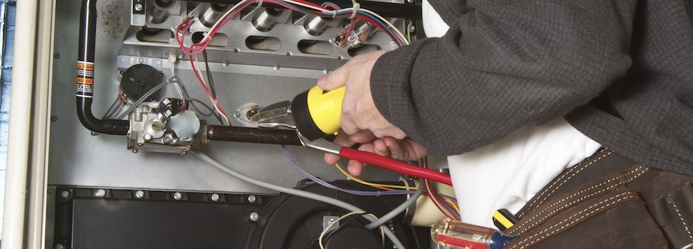Repairman servicing or repairing basement furnace unit